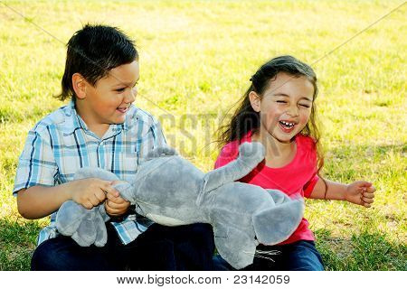 The boy with the girl play sitting on a grass