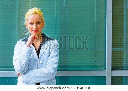 Pensive Business Woman With Hand Near Face Standing Near Office Building
