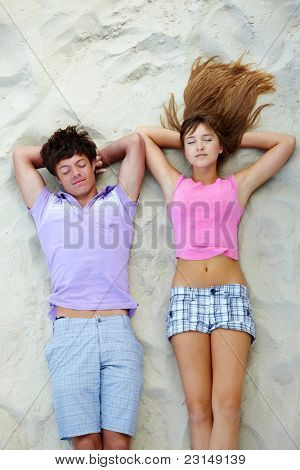 Above angle of teenage couple relaxing on sandy beach