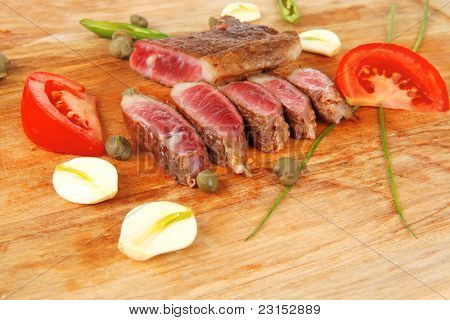 fresh roasted lamb meat fillet ready on wooden board with cutlery isolated  over white background