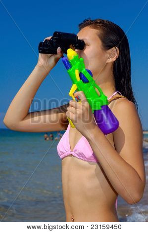 Woman with water-pistol looking through binocular at the beach