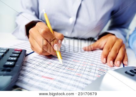 Photo of hands holding pencil over documents while working with papers