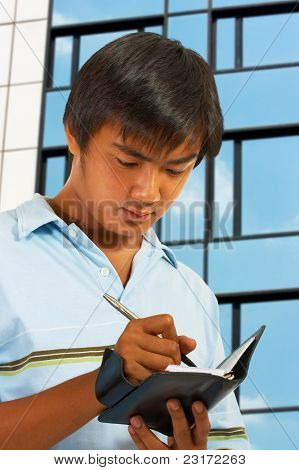 Man Writing In His Organizer