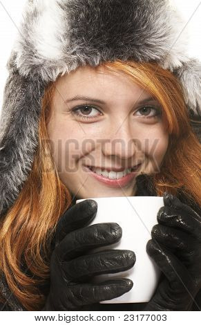smiling young redhead woman in winter dress holding coffee cup