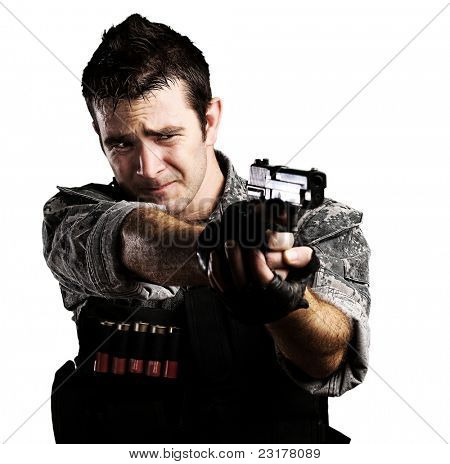 portrait of young soldier pointing with a gun against a white background