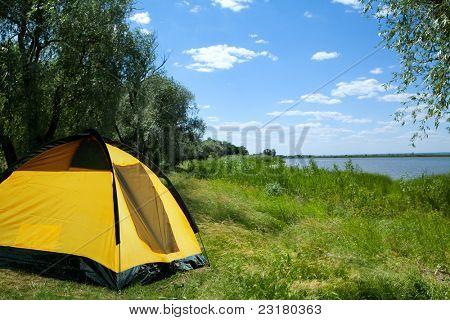 Tent yellow on the bank of lake