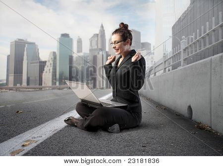 Triumphing businesswoman sitting on a city street and using a laptop