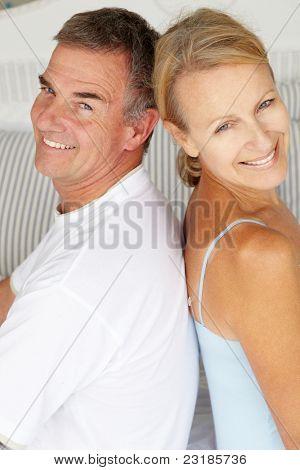 Sesión de la feliz pareja espalda con espalda en la cama