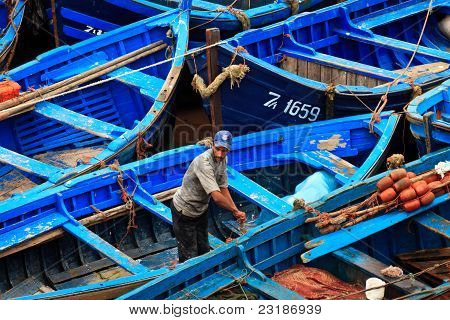 Fisherman And Blue Fishing Boats Crowded Togeter At Docks