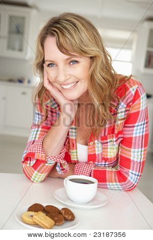 Mid age woman with coffee and biscuits at home