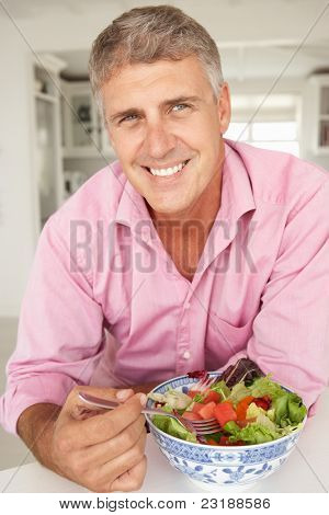 Mid age man eating salad