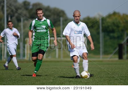 KAPOSVAR, HUNGARY - SEPTEMBER 5: Attila Kiss (white 5) in action at the Hungarian National Championship under 19 game Kaposvar (white) vs. Nagyatad (green) September 5, 2011 in Kaposvar, Hungary.