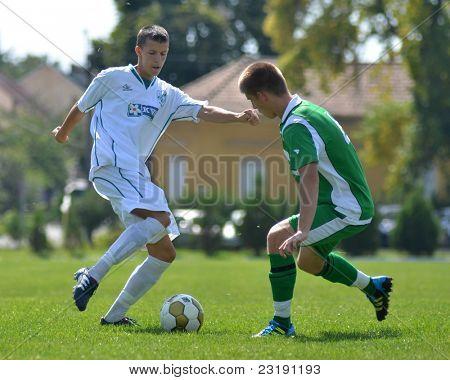 KAPOSVAR, HUNGARY - SEPTEMBER 5: Unidentified players in action at the Hungarian National Championship under 19 game Kaposvar (white) vs. Nagyatad (green) September 5, 2011 in Kaposvar, Hungary.