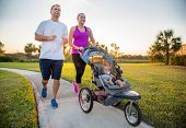Couple exercising and jogging together at the park pushing their baby in a stroller poster
