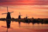 Netherlands rural lanscape with windmills at famous tourist site Kinderdijk in Holland on sunset wit poster