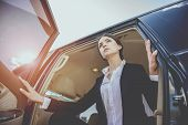 Young Beautiful Confident Businesswoman In Suit Coming Out Of Her Luxurious Car. poster