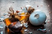Close Up Of Oil Of Onion Or Allium Cepa L Oil On A Wooden Surface With Raw Onions In Dark Gothic Col poster