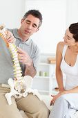 pic of chiropractor  - Chiropractor explaining the spine to a woman in a room - JPG