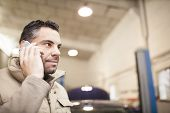 Mechanic Answers A Phone Call While Checking Vehicle Levels In A Mechanic Workshop poster