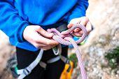 Постер, плакат: A Rock Climber Tie A Knot For Insurance