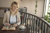 Young Smiling Blonde Woman With Glasses In A Restaurant Reading A Book And Drinking Coffee During A  poster