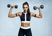 Beautiful Young Woman Doing Exercises With Dumbbells. Photo Athletic Woman With Perfect Body On Grey poster
