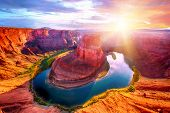Vivid dramatic sunset over Horseshoe Bend, a famous meander on river Colorado near the town of Page. poster
