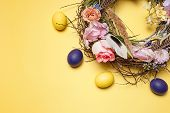 Easter Card. Painted Easter Eggs In Nest On Yellow Table Background. Top View Of Easter Decoration.  poster