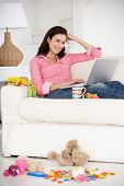 stock photo of untidiness  - Busy mother working on laptop - JPG