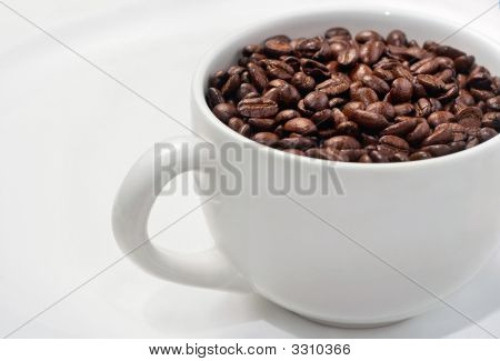 Simple White Cup Filled With Whole Coffee Beans