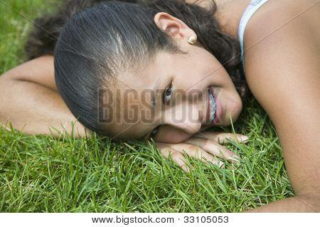 Hispanic girl laying in grass