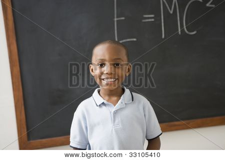 African American boy in front of black board