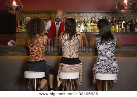 Hispanic women sitting at bar