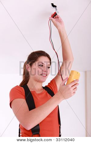 Woman using a voltmeter on ceiling electrics