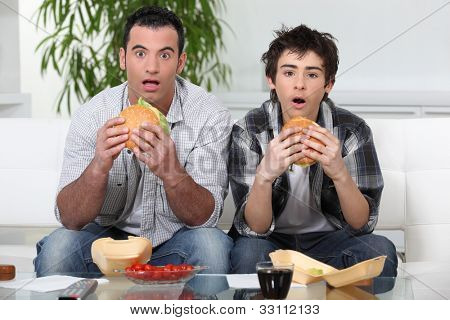 Brothers staring in amazement while eating a hamburger