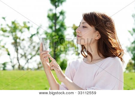 Beautiful young woman using a moblie phone in a park. Portrait o