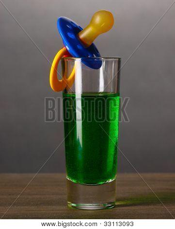 Bebé simulado con bebidas alcohólicas en fondo gris