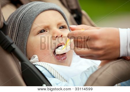 Mom feeding one-year old boy sitting in stroller