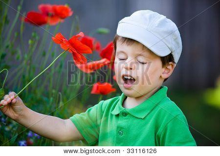 Cute little boy smells a flower
