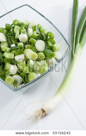 Spring onions, whole and sliced, close up