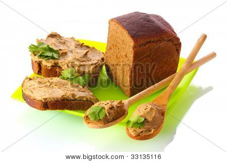Fresh pate on bread on green plate isolated on white