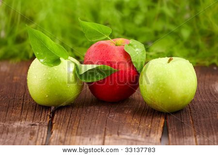 Three fresh wet apples with leaves on wooden board. Two green and one red.