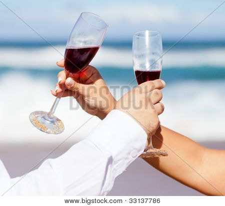 man and woman drinking champagne on beach