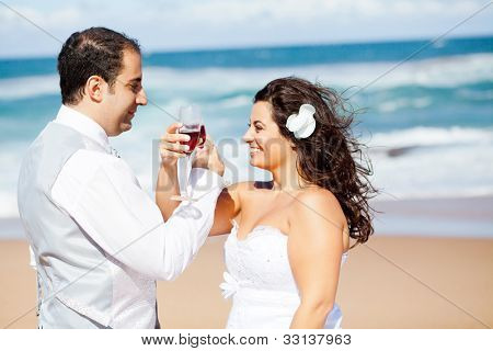 groom and bride drinking  champagne on beach