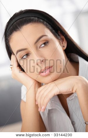 Closeup portrait of attractive woman with dark hair daydreaming.