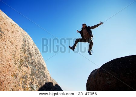 man jumping cliff with blue sky