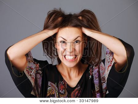 Stress. Woman stressed is going crazy pulling her hair in frustration.