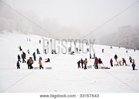 Children Are Skating At A Toboggan Run In Winter On Snow
