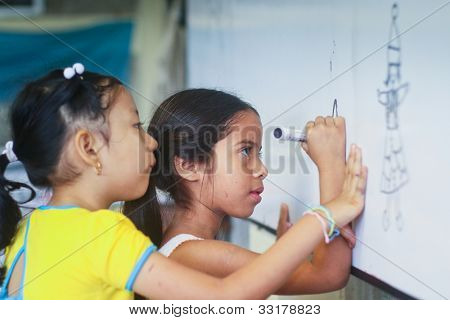 GUAYAQUIL, ECUADOR - FEBRUARY 8: Unknown children in lesson drawing in primary school by project to help deprived children in deprived areas with education, February 8, 2011 in Guayaquil, Ecuador.