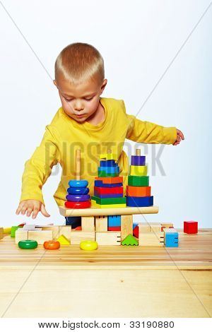 little 3 year old toddler boy playing with bright wooden pyramid over light studio background
